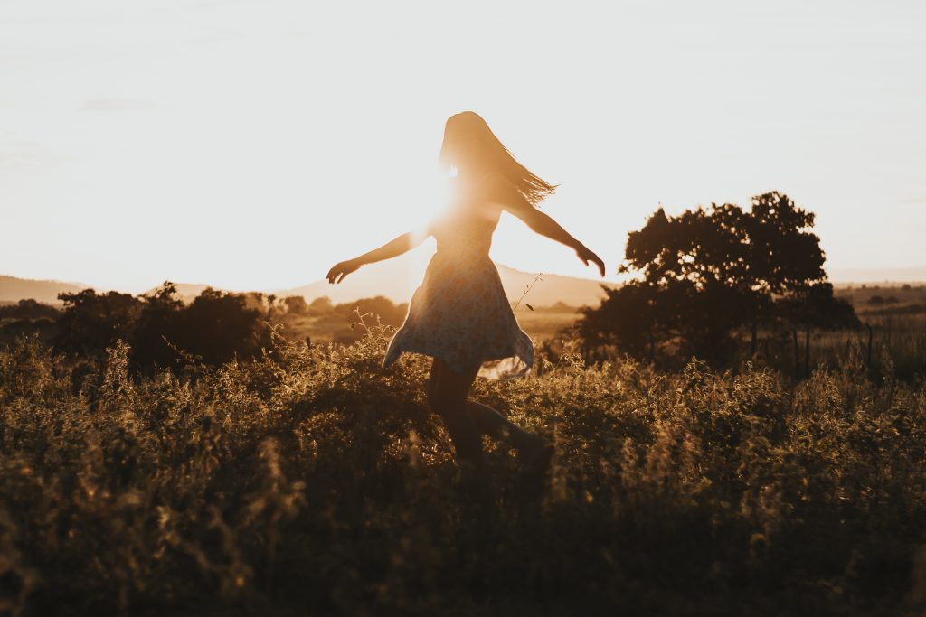 girl dancing in a field in the sun