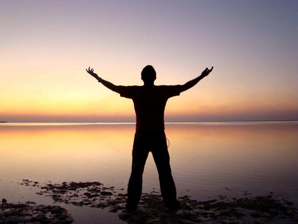 man celebrating success at sunset