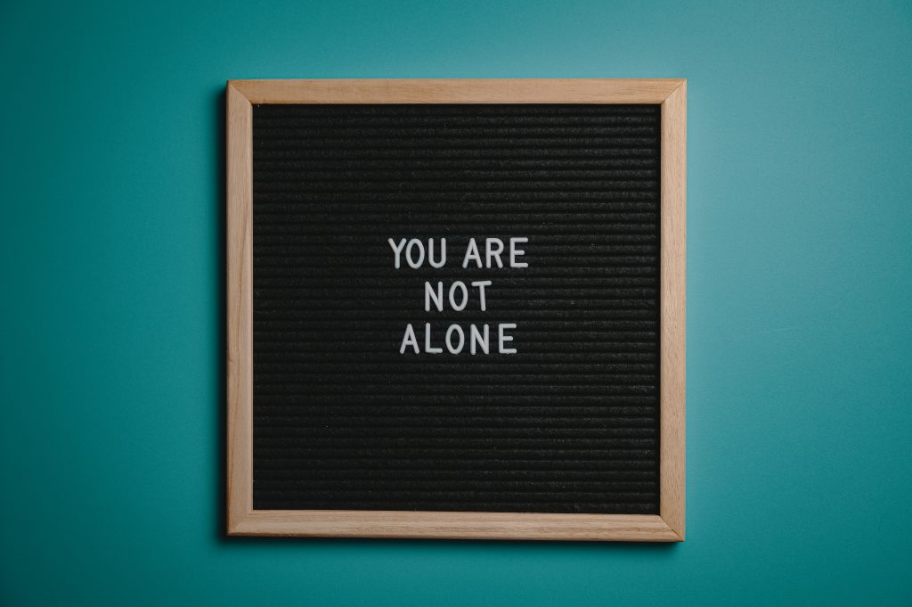 You are not alone written on a board