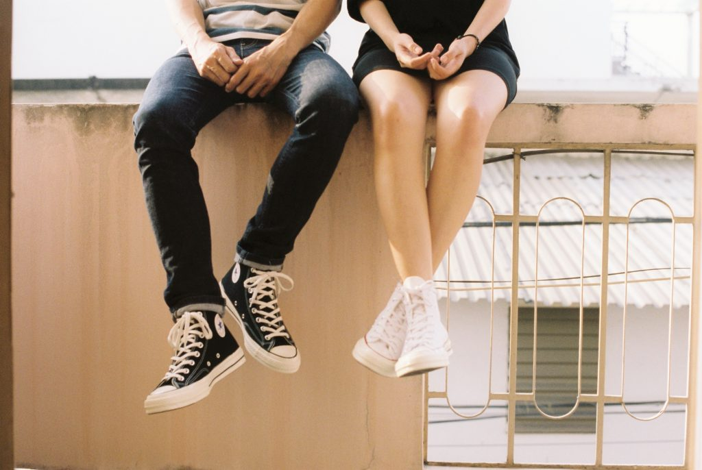 two people sitting on a wall