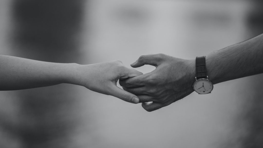 greyscale photo of two hands holding