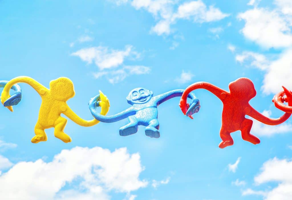 three different coloured monkey toys linking arms