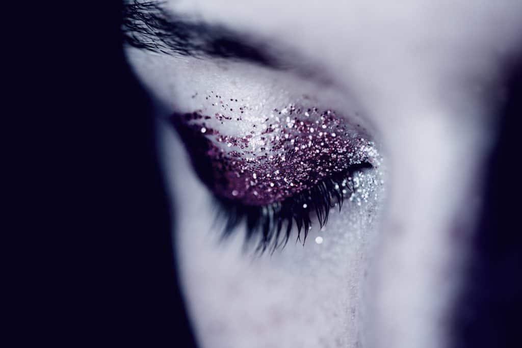 eye with glitter eyeshadow crying